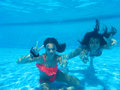 Girls underwater in pool two teenage swimming both giving a two finger x or v for victory x salute Stock Image