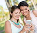 Girls using app on a mobile phone happy Royalty Free Stock Photography