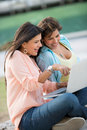 Girls using a laptop computer outdoors and looking very happy Stock Images