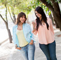 Girls using a mobile phone casual walking outdoors Royalty Free Stock Image