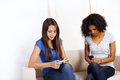 Girls using mobile phones Royalty Free Stock Photo