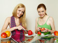 Girls with vegetables and fruit behind a table Royalty Free Stock Image