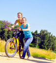 Girls walk up the hill with bicycle on village Royalty Free Stock Image