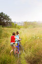 Girls walking bicycles in field two through rural summer Stock Photo