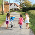 Girls walking and pushing a bike barefoot kids one girl bicycle two other aside Stock Photos
