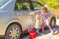 Girls washing the car cute young are helping their dad by Royalty Free Stock Images