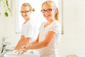 Girls are washing hands in the bath children sisters or daughter with friends at washbasin Stock Images
