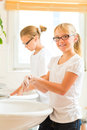 Girls are washing hands in the bath children sisters or daughter with friends at washbasin Royalty Free Stock Images