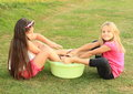 Girls washing their feet smiling sitting on grass and Royalty Free Stock Photography
