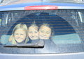 Girls watching from car trunk three smiling close together loaded in closed of a silver Stock Images