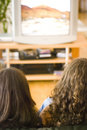 Girls watching tv Stock Photography
