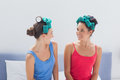 Girls wearing hair rollers sitting in bed Royalty Free Stock Photo