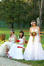 Girls in a wedding dresses one girl standing two young women sitting on bench the park Stock Photo