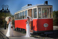 Girls in a wedding dresses with parasols standing front of the tram Stock Image