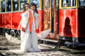 Girls in a wedding dresses with parasols standing front of the tram Royalty Free Stock Photo