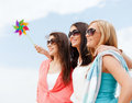 Girls with windmill toy on the beach summer holidays vacation and ecology concept Royalty Free Stock Photography