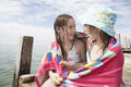 Girls wrapped in towel sitting on jetty cute looking at each other while Stock Photography