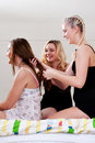 Girs doing each others hair on bed Royalty Free Stock Photos