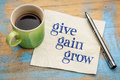 Give gain and grow personal development concept handwriting on a napkin with a cup of coffee Royalty Free Stock Image