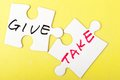 Give and take words written on two pieces of puzzle Royalty Free Stock Photos