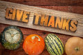 Give thanks word abstract in wood type thanksgiving concept letterpress over a grained cedar plank against rustic barn with Royalty Free Stock Photography