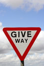 Give way road sign closeup of against cloudy sky Stock Photos