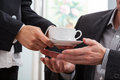 Giving a cup of coffee woman hands to businessman Royalty Free Stock Images