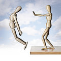 Giving a good shove two manikins one pushing the other off an edge Royalty Free Stock Images