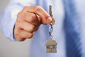Giving house keys holding out on a shaped keychain Royalty Free Stock Photos