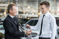 Giving a key of a brand new car handsome young classic salesman to the owner and smiling Stock Photo