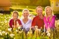 Glückliche Familie, die in der Sommerwiese sitzt Lizenzfreies Stockfoto
