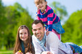 Glückliche familie die in der sommerwiese sitzt Stockfotos