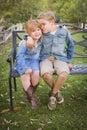 Glücklicher junger bruder und schwester sitting together outside Stockbild