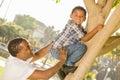 Glücklicher mischrasse vater helping son climb ein baum Stockfotos