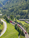 Glacier express panorama train crossing green rural valley vallais switzerland aerial view on Royalty Free Stock Photo