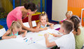 Glad kids drawing on lesson in elementary school class Royalty Free Stock Photo