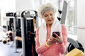 Glad retiree looking at mobile in gym