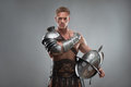 Gladiator in armour posing with helmet over grey half length portrait of young handsome muscular man isolated background Stock Images