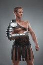 Gladiator in armour posing over grey background half length portrait of young handsome muscular man pointing aside isolated Stock Photo