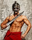 Gladiator with muscular body sword and helmet Royalty Free Stock Photos
