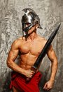Gladiator with muscular body sword and helmet Royalty Free Stock Image