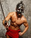 Gladiator with muscular body sword and helmet Royalty Free Stock Photo