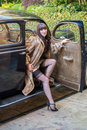 Glamor model wearing a fur coat and stockings glamorous high heels nylon gets out of classic car Stock Photos