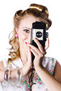 Glamorous blond woman photographer taking picture retro film camera white background Stock Photography