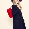 Glamorous blonde in classic black coat and red hat. Autumn fashi Royalty Free Stock Photo
