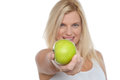 Glamorous blonde offering you juicy green apple Stock Image