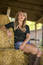 Glamorous blonde woman posing dressed in dark jumper blue denim shorts and leather boots sitting on straw bales Royalty Free Stock Photo