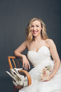 Glamorous bride displaying her bridal shoes and flowers while sitting in a relaxed position in a wooden chair looking at the Stock Photos