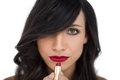 Glamorous brunette applying red lipstick on white background Royalty Free Stock Photo