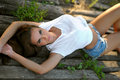 Glamorous brunette lying on old wooden planks Royalty Free Stock Photo